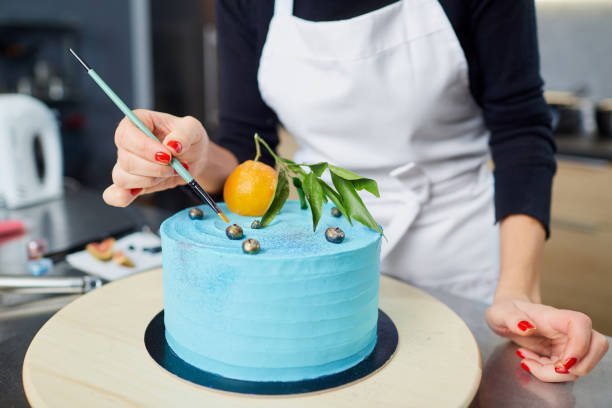 The confectioner decorates the cake on the table in the kitchen. The confectioner decorates the cake on the table in the kitchen in the pastry shop. decorating a cake stock pictures, royalty-free photos & images