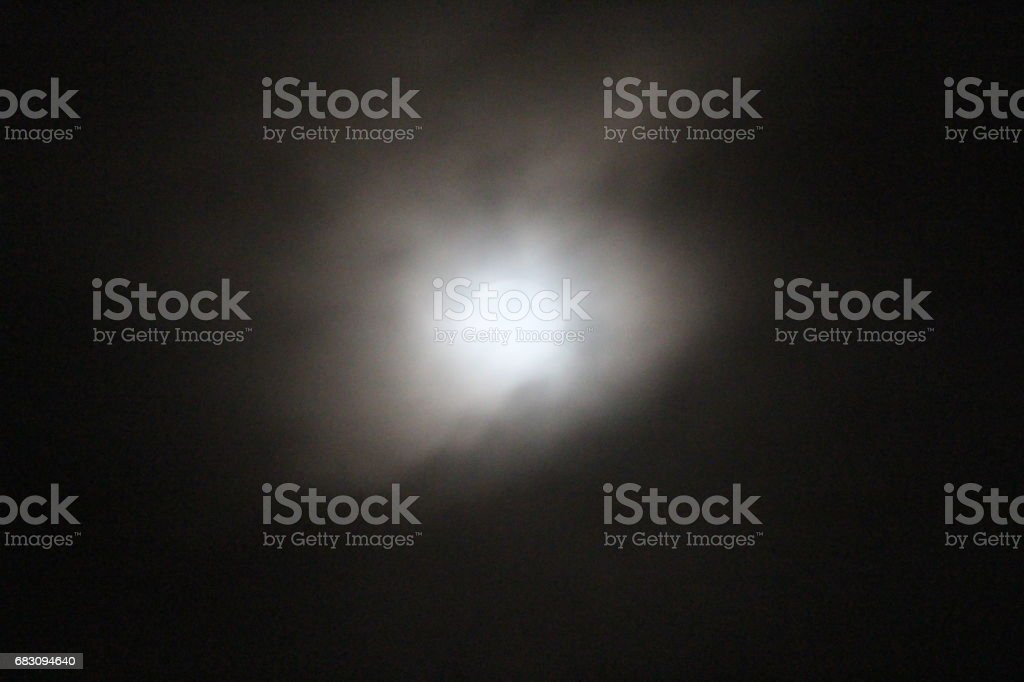 The conflict between the clouds and the moon The clouds strongly want to obscure the moonlight and the moon will only illuminate the darkness of the sky foto de stock royalty-free