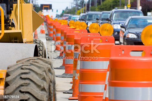 A row of bright Orange construction barriers separate construction from the busy traffic.