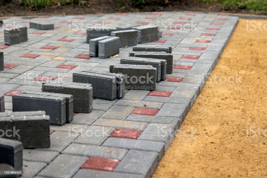 The construction of the sidewalk. Gray and brown blocks on a sandy gravel foundation. - Foto stock royalty-free di A forma di blocco