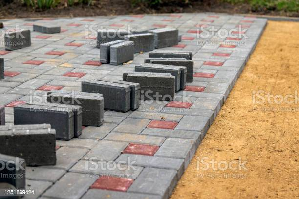 The Construction Of The Sidewalk Gray And Brown Blocks On A Sandy Gravel Foundation - Fotografie stock e altre immagini di A forma di blocco