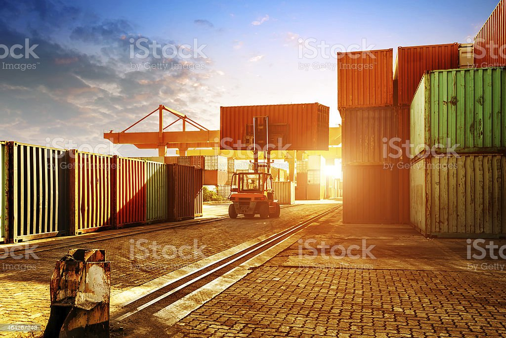 The container terminal at dusk When the container terminal at dusk, work cranes and forklift. Box - Container Stock Photo