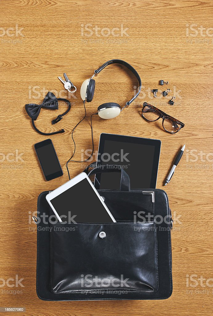 The contents of modern business briefcase on a wooden desk. stock photo