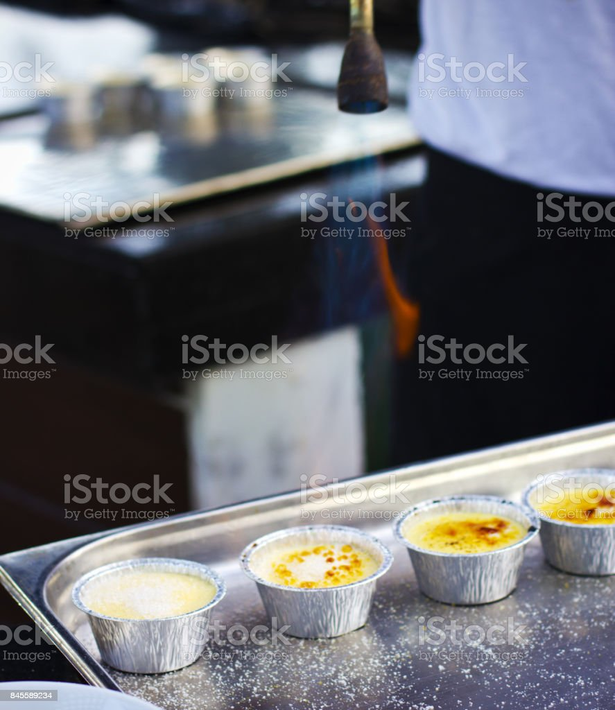 the cook caramelizes sugar on a cream brule. stock photo