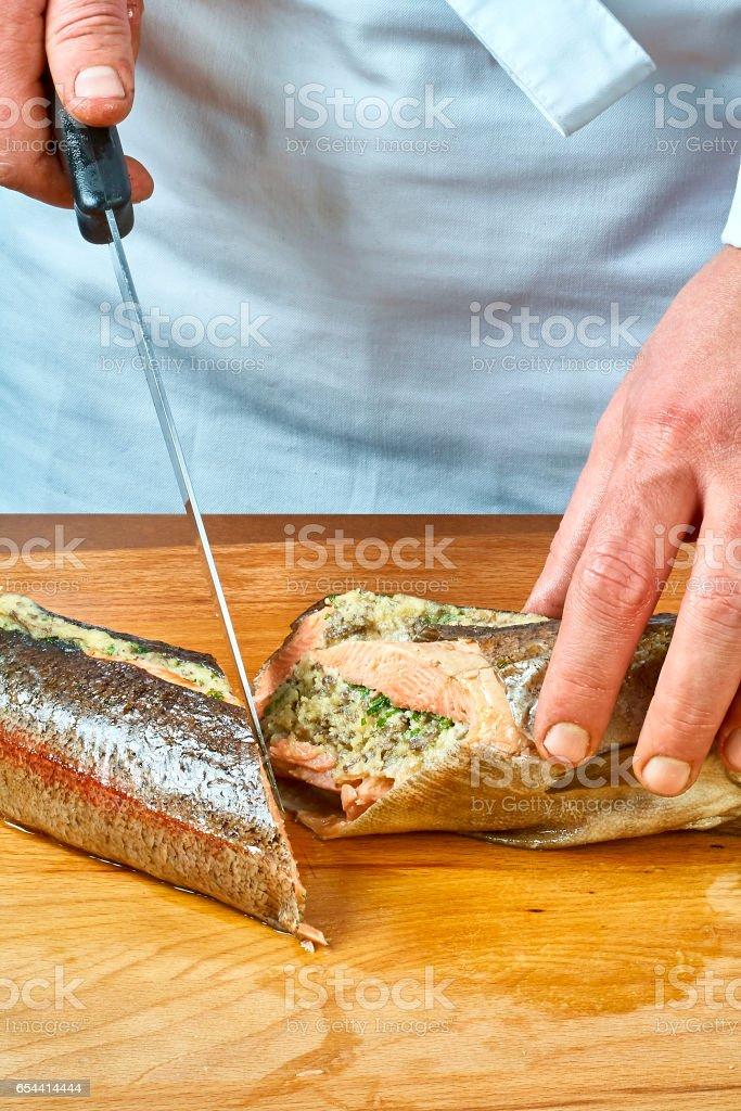 El Cocinero Corta El Pescado Al Horno Toda Una Colección De Recetas De Comida Foto De Stock Y Más Banco De Imágenes De Al Horno