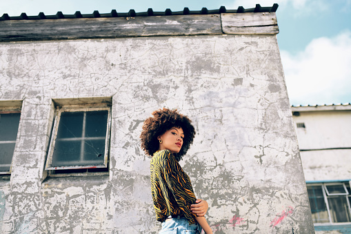Portrait of an attractive and stylish young woman posing against an urban background