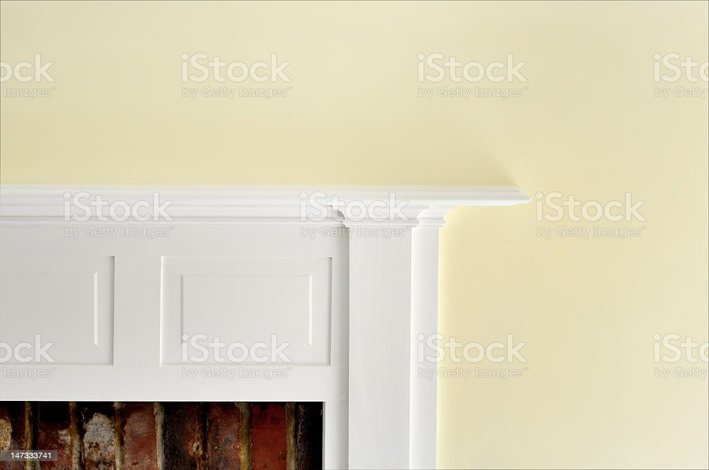 The corner of a fireplace surround in white stock photo