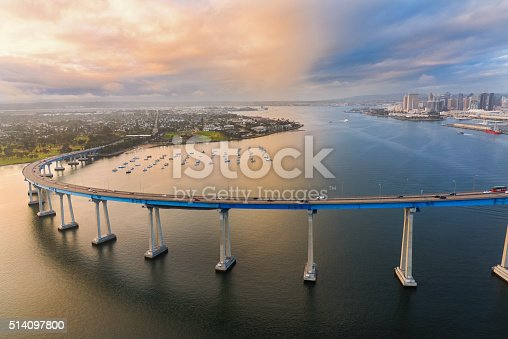 The iconic Coronado Bridge spanning the San Diego Bay with the city's skyline in the background shot at dusk after a storm began to clear.  I shot this photograph from approximately 300 feet in elevation during a chartered helicopter photo-flight of the region.