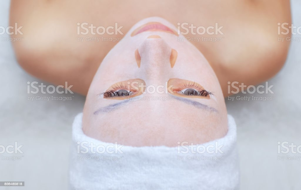 The cosmetologist for procedure of cleansing and moisturizing the skin, applying a sheet mask to the face of a young woman in beauty salon. stock photo