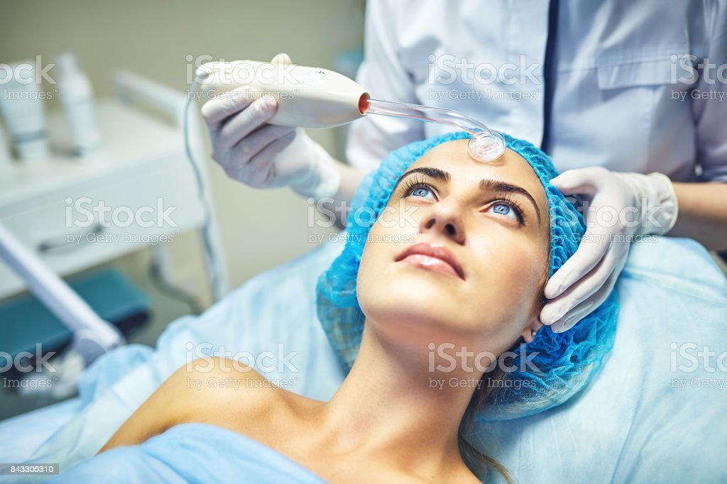 The cosmetologist is caring for the patient's face stock photo