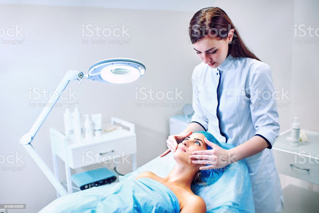 The cosmetologist is caring for the patient's face – zdjęcie