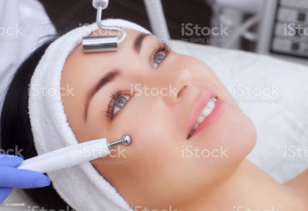 The cosmetologist makes the apparatus a procedure of Microcurrent therapy of a beautiful, young woman in a beauty stock photo