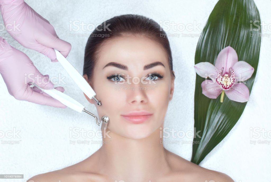 The cosmetologist makes the apparatus a procedure of Microcurrent therapy of a beautiful, young woman in a beauty salon stock photo