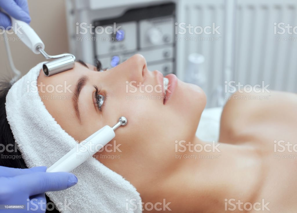 The cosmetologist makes the apparatus a procedure of Microcurrent therapy of a beautiful, young woman in a beauty salon. stock photo
