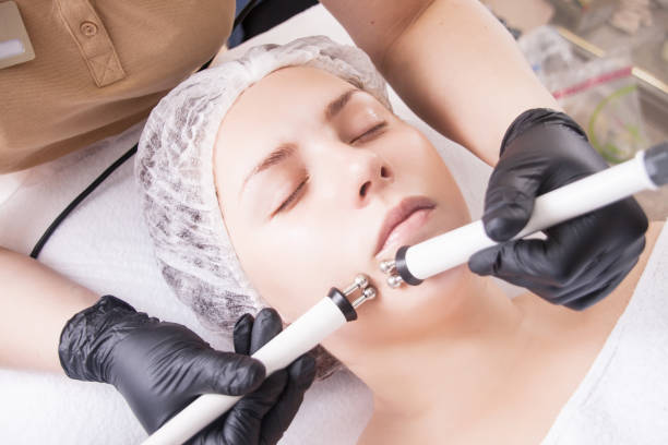 The cosmetologist makes the apparatus procedure of Microcurrent therapy of a beautiful, young woman in a beauty salon. The cosmetologist makes the apparatus a procedure of Microcurrent therapy of a beautiful, young woman in a beauty salon. Cosmetology and professional skin care. rymdraket stock pictures, royalty-free photos & images