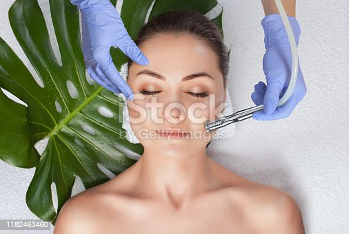 istock The cosmetologist makes the  Microdermabrasion procedure of the facial skin of a woman in a beauty salon.Cosmetology and professional skin care. 1182463460