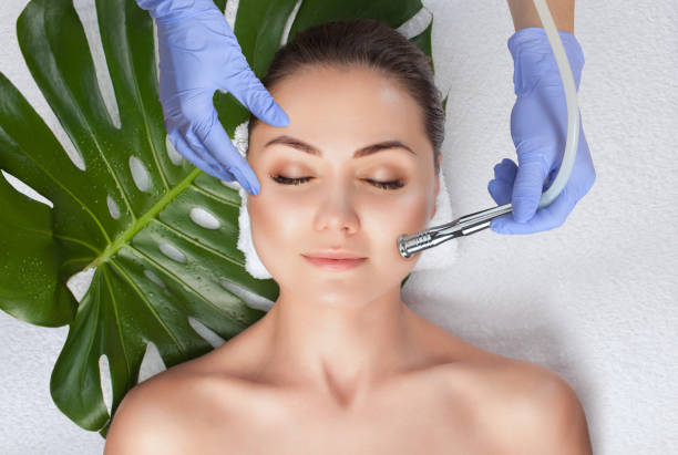 The cosmetologist makes the  Microdermabrasion procedure of the facial skin of a woman in a beauty salon.Cosmetology and professional skin care. stock photo
