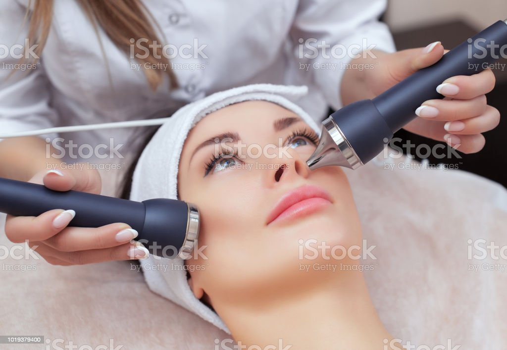 The cosmetologist makes the procedure an ultrasonic cleaning of the facial skin of a beautiful, young woman in a beauty salon stock photo