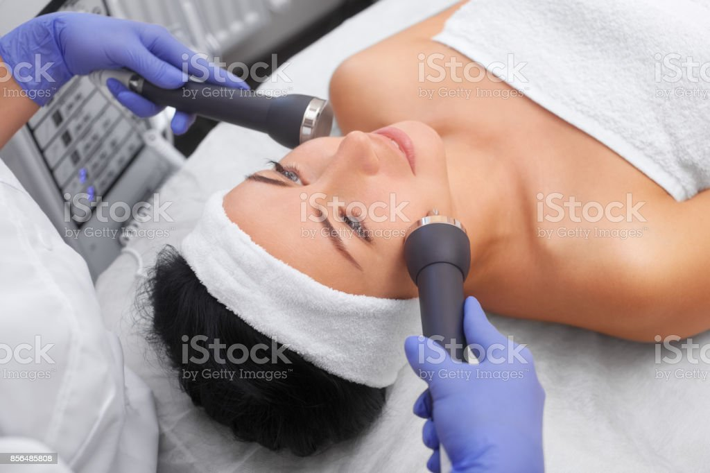 The cosmetologist makes the procedure an ultrasonic cleaning of the facial skin of a beautiful, young woman in a beauty salon. stock photo
