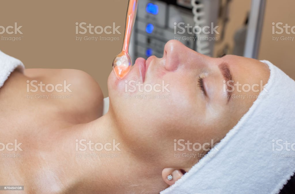 The cosmetologist makes the procedure Microcurrent therapy of the facial skin of a beautiful, young woman stock photo