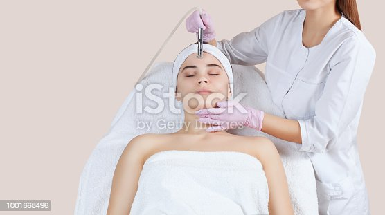 istock The cosmetologist makes the procedure Microdermabrasion of the facial skin of a beautiful, young woman in a beauty salon 1001668496