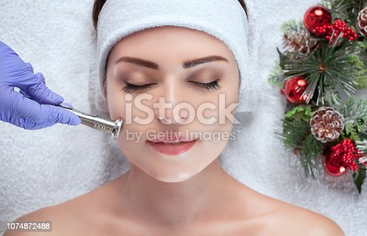 istock The cosmetologist makes the procedure Microdermabrasion of the facial skin of a beautiful, young woman in a beauty salon. 1074872488