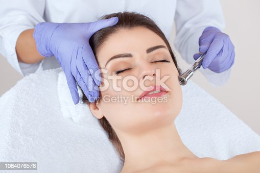 istock The cosmetologist makes the procedure Microdermabrasion of the facial skin of a beautiful, young woman in a beauty salon. 1084076576