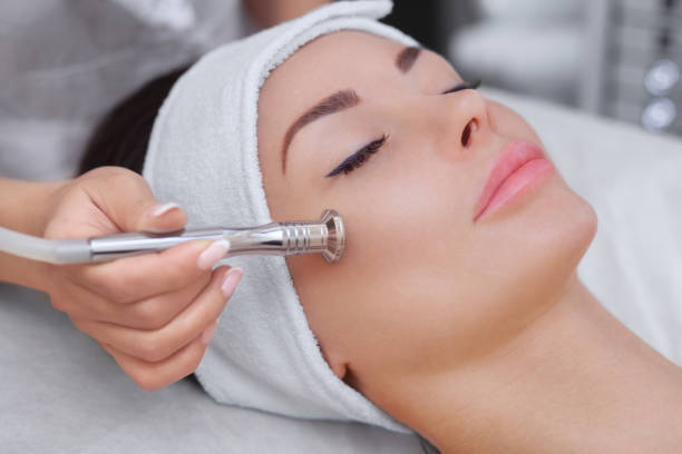 The cosmetologist makes the procedure Microdermabrasion of the facial skin of a beautiful, young woman stock photo