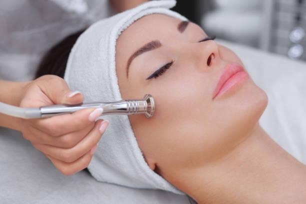 美容師は、美しい、若い女性の顔の皮膚のマイクロダーマブレーションの手順になります ストックフォト