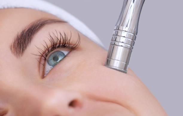 L'esthéticienne rend la procédure Microdermabrasion de la peau du visage - Photo