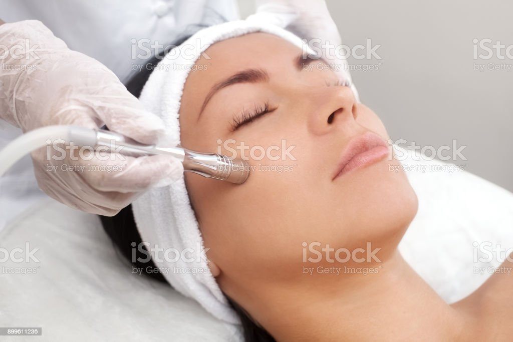 The cosmetologist makes the procedure Microdermabrasion of the facial skin of a beautiful, young woman in a beauty salon foto stock royalty-free