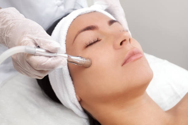 The cosmetologist makes the procedure Microdermabrasion of the facial skin of a beautiful, young woman in a beauty salon stock photo