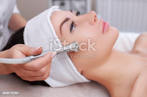 istock The cosmetologist makes the procedure Microdermabrasion of the facial skin of a beautiful, young woman 908578260