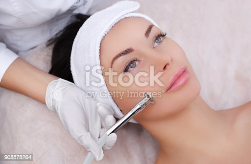 istock The cosmetologist makes the procedure Microdermabrasion of the facial skin of a beautiful, young woman 908578264