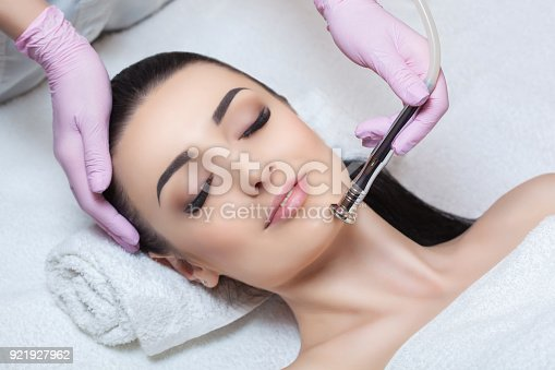 istock The cosmetologist makes the procedure Microdermabrasion of the facial skin of a beautiful, young woman in a beauty salon 921927962