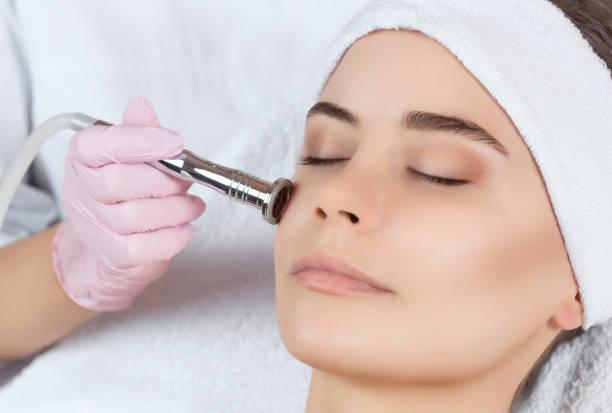 美容師は、美容サロンでプロシージャ マイクロダーマブレーション美しい、若い女性の顔の皮膚のようになります ストックフォト