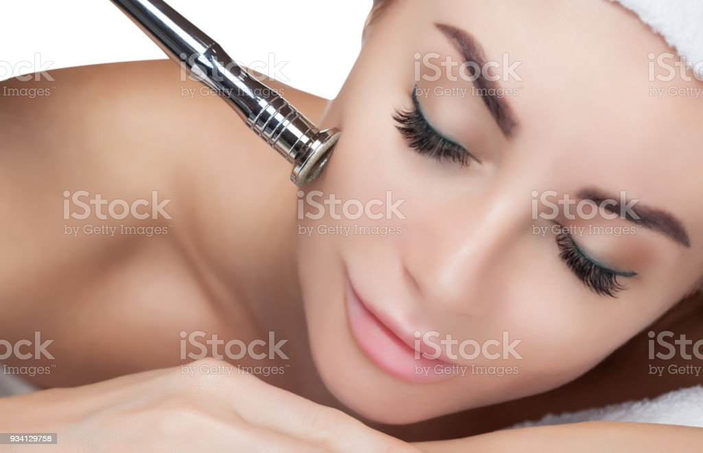 The cosmetologist makes the procedure Microdermabrasion of the facial skin of a beautiful, young woman in a beauty salo stock photo