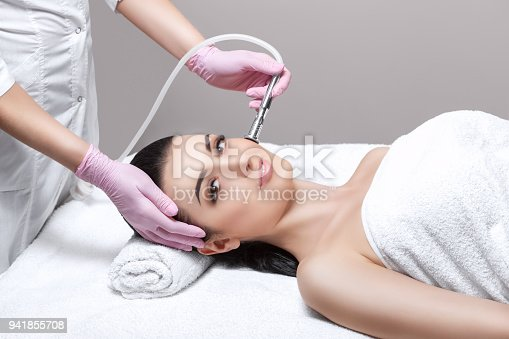 istock The cosmetologist makes the procedure Microdermabrasion of the facial skin of a beautiful, young woman in a beauty salon. 941855708