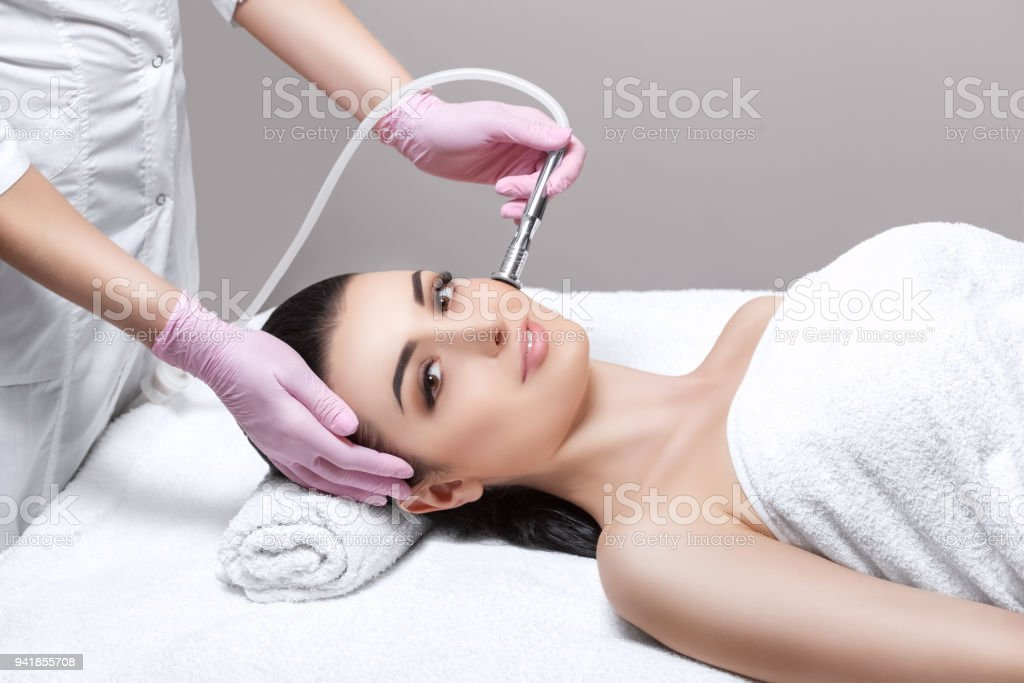 The cosmetologist makes the procedure Microdermabrasion of the facial skin of a beautiful, young woman in a beauty salon. stock photo