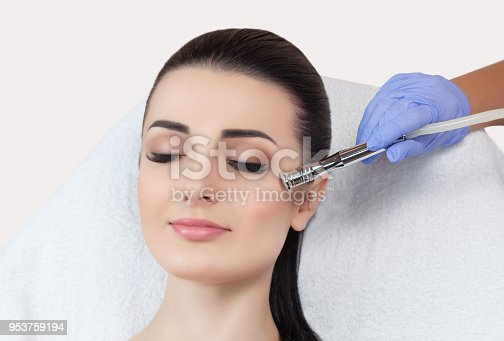 istock The cosmetologist makes the procedure Microdermabrasion of the facial skin of a beautiful, young woman in a beauty salon. 953759194