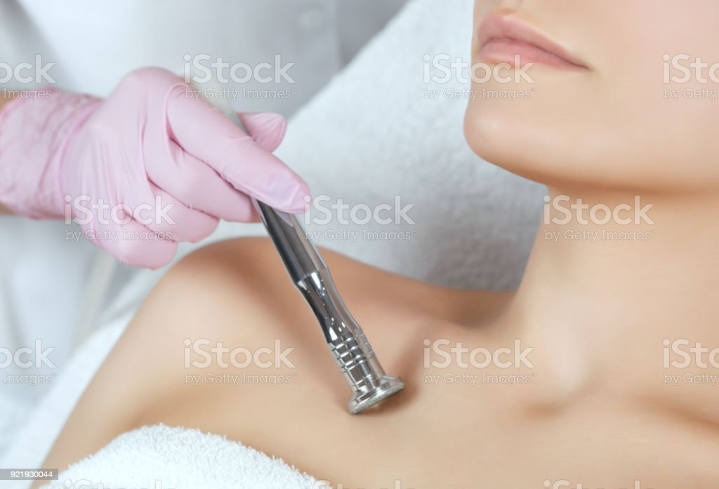 The cosmetologist makes the procedure Microdermabrasion of the decollete skin of a beautiful, young woman in a beauty salon stock photo
