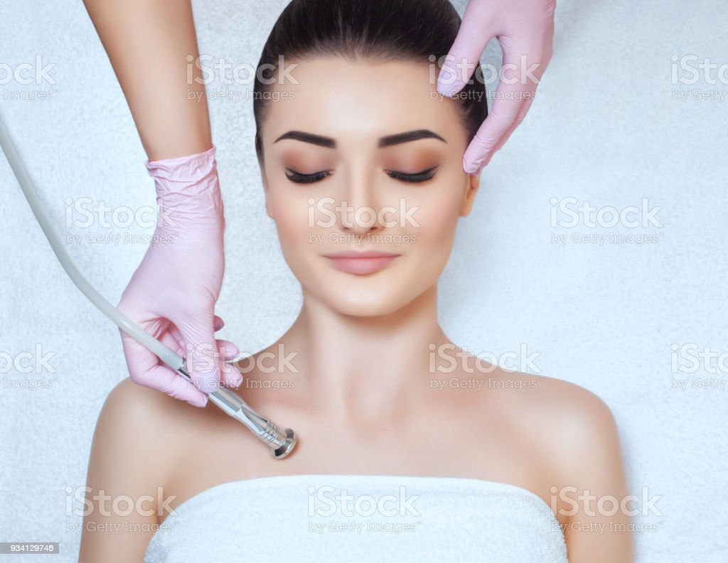 The cosmetologist makes the procedure Microdermabrasion of the décolletage skin of a beautiful, young woman in a beauty salon stock photo