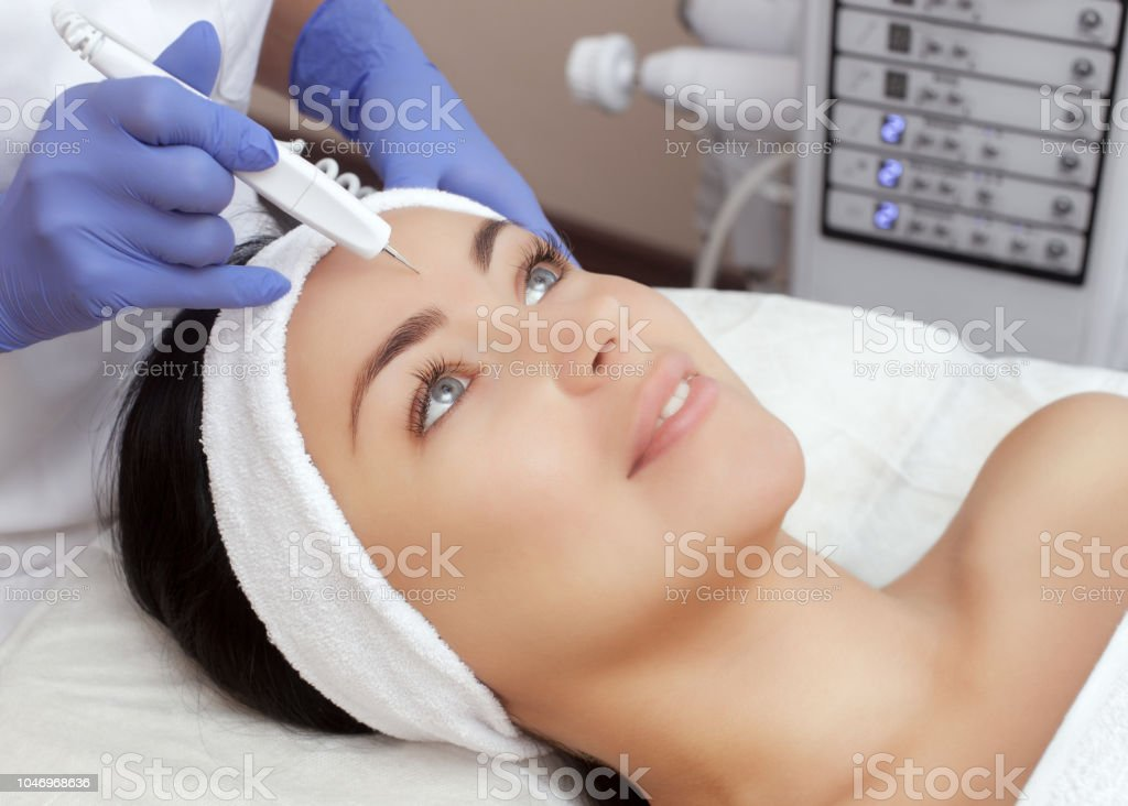 The cosmetologist makes the procedure treatment of Couperose of the facial skin of a beautiful, young woman in a beauty salon. stock photo