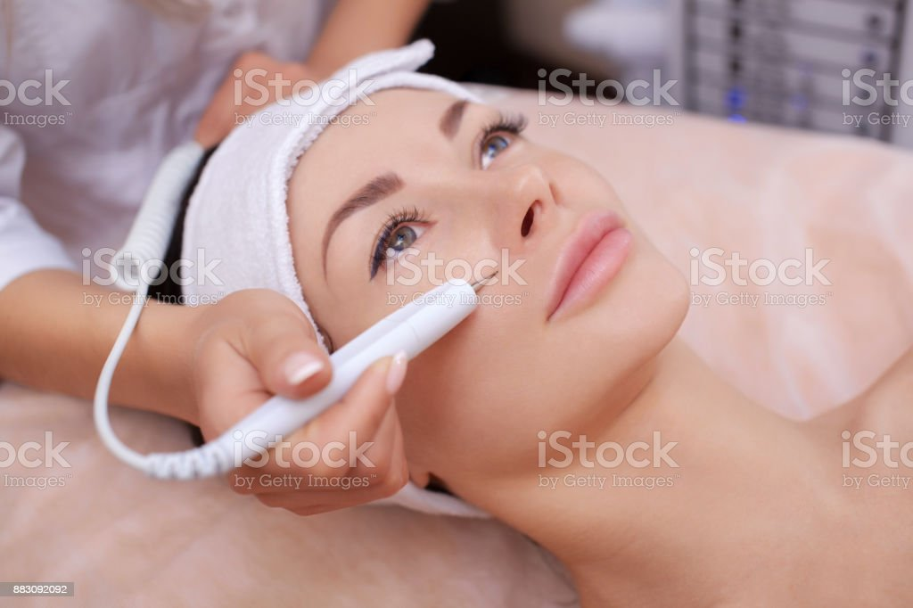 The cosmetologist makes the procedure treatment of Couperose of the facial skin stock photo