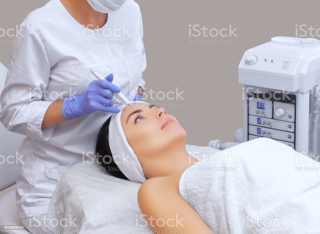 The cosmetologist makes the procedure treatment of Couperose of the facial skin of a beautiful, young woman in a beauty salon stock photo