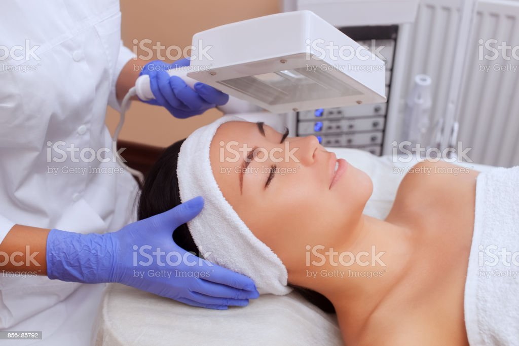 The cosmetologist uses the Wood Lamp for detailed diagnosis of the skin condition. stock photo
