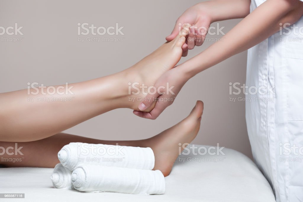 The cosmetologist wraps the leg of the customer. - Foto stock royalty-free di Accudire