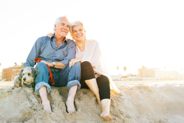 The cost of retirement happiness Senior couple on the beach 65 69 years stock pictures, royalty-free photos & images