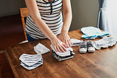 Cropped shot of a pregnant woman sorting baby clothes at home