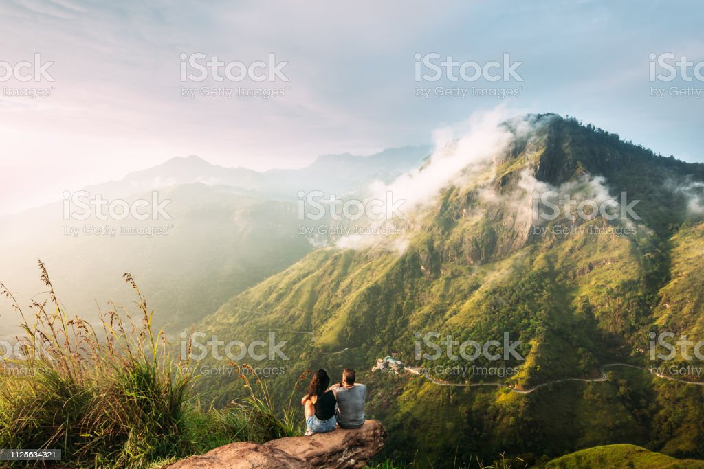 The couple greets the sunrise in the mountains. Man and woman in the...